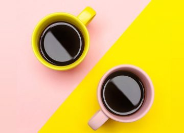 Flat lay top view of a two coffee cups with pink and yellow.